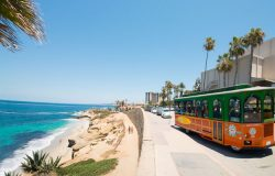 old town trolley driving by la jolla beach for first time visitors to san diego