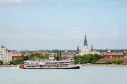 natchez riverboat, a new orleans riverboat, coasting along the water with city behind