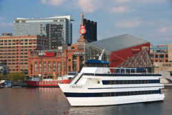 ship touring through inner harbor baltimore with restaurants in back