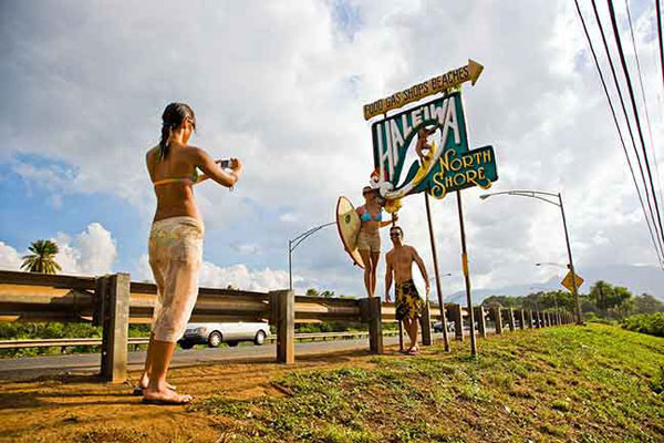 Woman taking photograph at Oahu's North Shore sign
